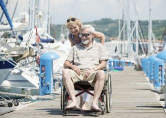 A man in a wheelchair visits the seaside with his wife