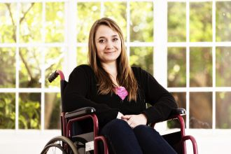A girl in a wheelchair with a Spinal Cord Injury