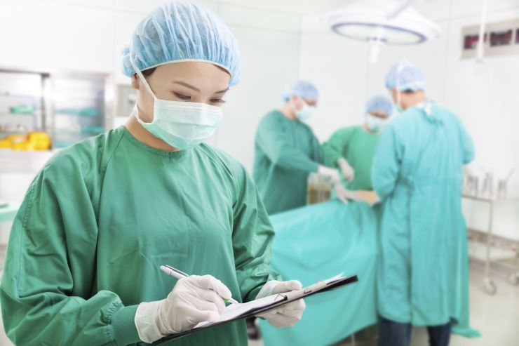A sugeon takes notes in the operating theatre