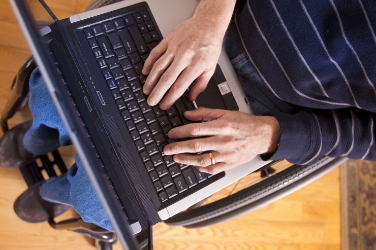 A man in a wheelchair uses a laptop